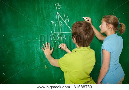 Portrait of two classmates by the blackboard at the lesson of geometry