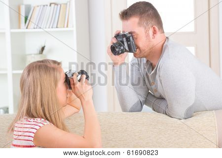 Young couple at home taking pictures with old analog SLR cameras