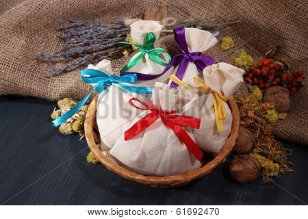Textile sachet pouches with dried flowers, herbs and berries on wooden table, on sackcloth background