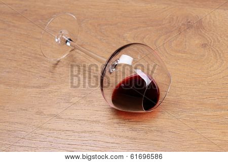 Overturned glass of wine on floor close-up