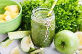 stock photo of fruit  - Fresh organic green smoothie with salad apple cucumber pineapple and lemon as healthy drink - JPG