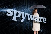 Businesswoman holding umbrella behind the word spyware against circuit board