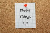 foto of upside  - The phrase Shake Things Up on a piece of graph paper pinned to a cork notice board - JPG