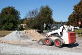 stock photo of earth-mover  - small excavator bobcat on the construction site - JPG