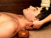foto of low-necked  - Masseur doing neck massage on man in the spa salon - JPG