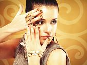 foto of minx  - Beautiful woman with golden nails and beautiful gold ring over creative background - JPG