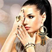Portrait of the beautiful fashion woman with black makeup and golden manicure