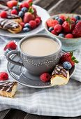image of eclairs  - Cup of coffee and chocolate eclairs with fresh berries - JPG