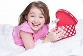 image of nighties  - Portrait of little happy girl with a gift lying on the bed  - JPG