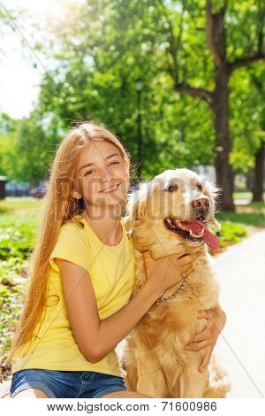 Teenage blonde girl with retriever dog otside