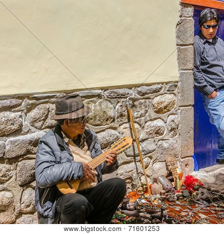CUZCO, PERU, MAY 1, 2014: Street seller of souvenirs plays the