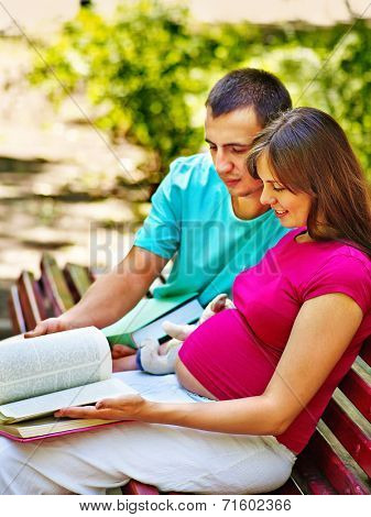 Pregnant woman, reading book with man  outdoor in park.