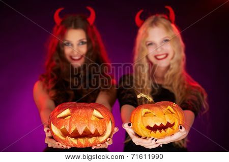 Two carved Halloween pumpkins on female palms