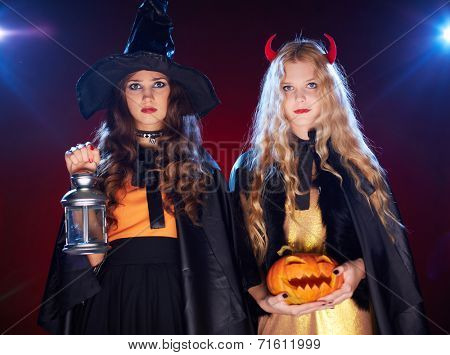Two eerie girls with lantern and pumpkin looking at camera in darkness