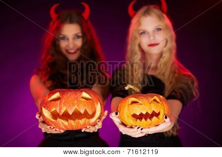 Two carved Halloween pumpkins held by females