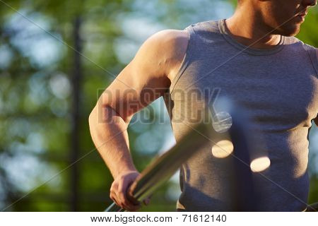 Sportsman in grey vest training on sport equipment outside