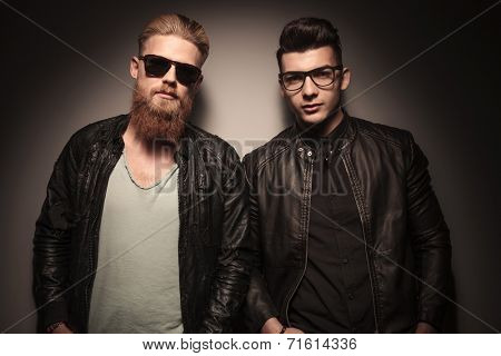 Two hot guys in leather jacket with glasses, looking at the camera, against studio background