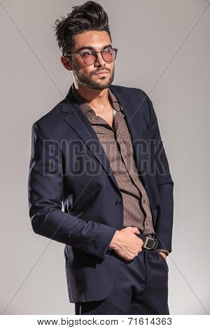 side view of a sexy young man in nice suit and shirt wearing glasses and holding his belt on grey background