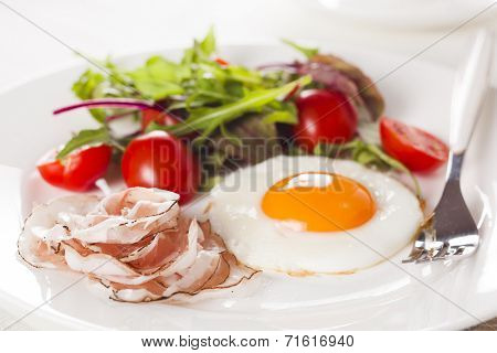Breakfast with eggs, ham and fresh salad.