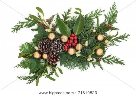 Christmas and winter decoration with holly, gold baubles, mistletoe, fir and cedar leaf sprigs with pine cones over white background.