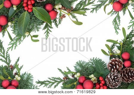 Christmas background border with red bauble decorations, holly, mistletoe, ivy, fir and cedar leaf sprigs with pine cones over white background.