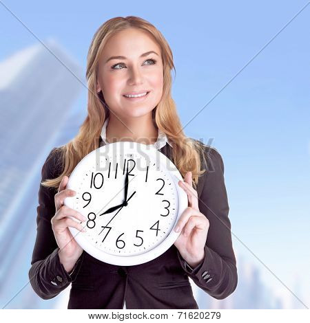 Portrait of happy smiling business woman holding in hands big clock outdoors, come to work on regular schedule, success concept