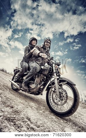 Active couple riding on the motorbike, slow motion, having fun in bikers tour, vintage style photo, happy adventure concept