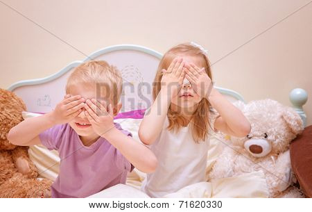 Little brother and sister play in hide and seek at home, covered eyes with hands, having fun together, family relationship, happy childhood concept