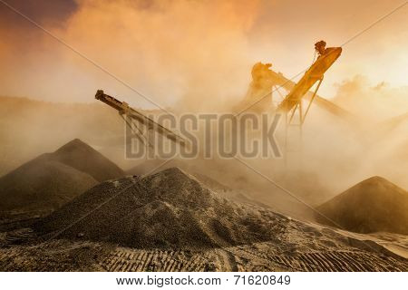Industrial hell pollution background concept - crusher (rock stone crushing machine) at open pit mining and processing plant for crushed stone, sand and gravel on sunset