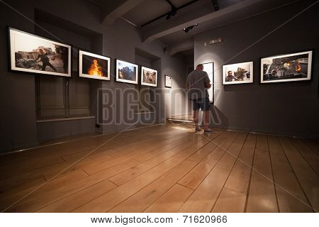 DUBROVNIK, CROATIA - MAY 26, 2014: Tourist looking at photos in the War photo limited gallery. There is 350m2 of exhibition space on two floors.