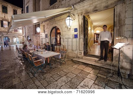 DUBROVNIK, CROATIA - MAY 27, 2014: Waiter standing at the entrance of Proto restaurant. Dubrovnik has many restaurants which offer traditional Dalmatian cuisine and some great wine lists.