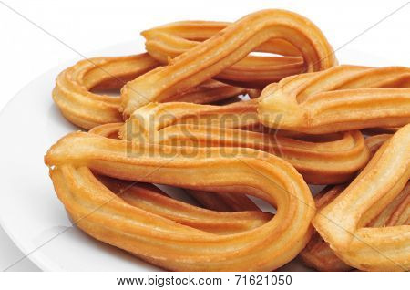 closeup of a plate with churros typical of Spain on a white background
