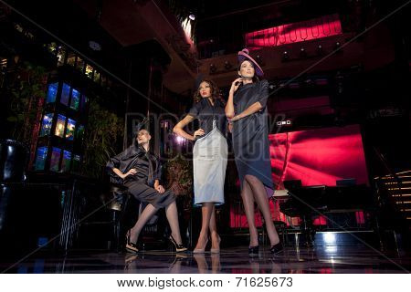 Three beautiful models in a stylish designer clothes posing in a nightclub