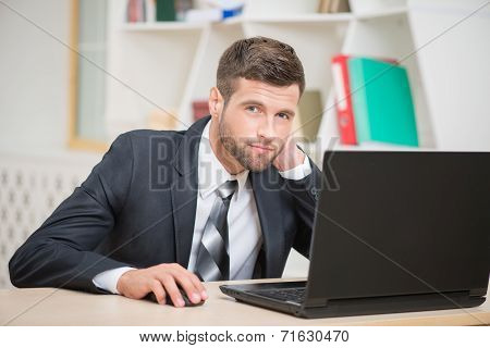 Businessman sitting at the table and working with laptop in offi