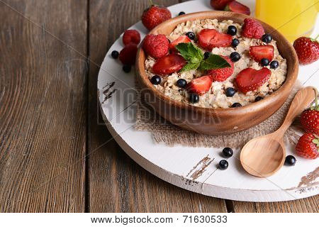 Tasty oatmeal with berries on table close-up
