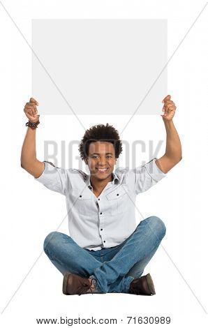Portrait Of Smiling African Man Sitting And Showing Blank Placard Isolated On White Background