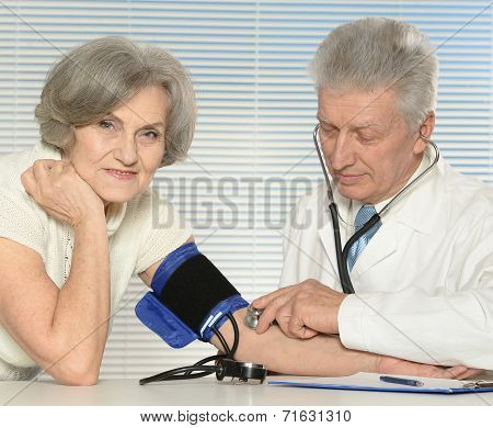 Elderly doctor measuring blood pressure