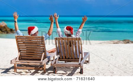 Back view of a happy couple in Santa hats relaxing on a tropical beach during Christmas vacation, panorama perfect for banners