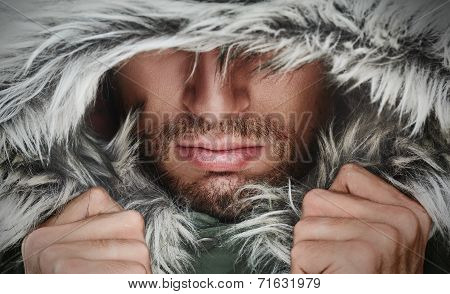 Brutal Face Of A Man With Beard Bristles And Hooded Winter