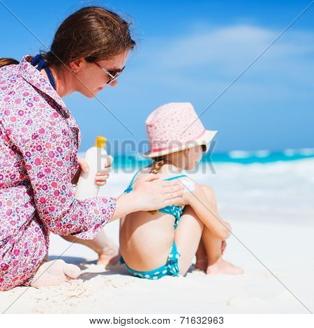 Mother applying sunblock cream on her daughters shoulder