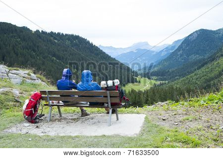 LA BALME, FRANCE - AUGUST 25: Hikers doing the Mont Blanc tour resting on bench in La Balme overlooking La Rollaz. The tour crosses France, Italy and Switzerland. August 25, 2014 in La Balme.