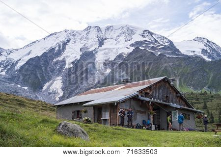 ST-GERVAIS-LES-BAINS, FRANCE - AUGUST 25: Hikers at the Truc Hostel, at bottom of the Domes de Miage mountain. This is one of the stages of the Mont Blanc Tour August 25, 2014 in St-Gervais-les-Bains.