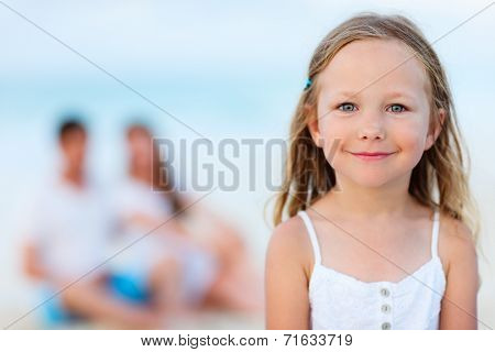 Adorable little girl and her family on a beach vacation