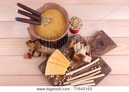 Fondue, biscuits, slices of cheese and rusks on cutting board on wooden background