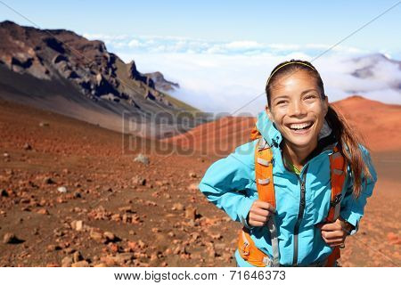 Woman walking and smiling happy, looking at beautiful nature landscape of mountain, East Maui Volcano, Haleakala national park Hawaii, USA.