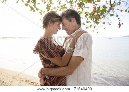 Portrait of a middle aged couple in love on the beach hugging