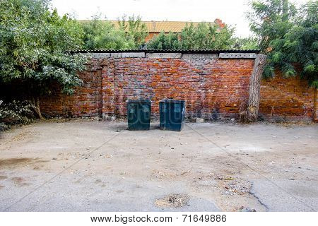 Two green dustbins outside against red brick wall