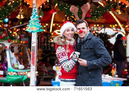 Man and woman or  a couple  or friends during advent season or holiday in front of a carousel or