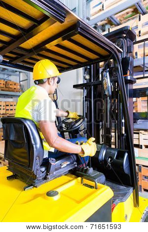 Asian fork lift truck driver lifting pallet in storage warehouse