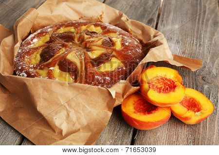 Delicious cake with peaches on wooden table close up